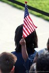 A toddler in the audience waving and American flag.