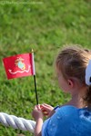 A little girl waving a U.S. Marine flag.