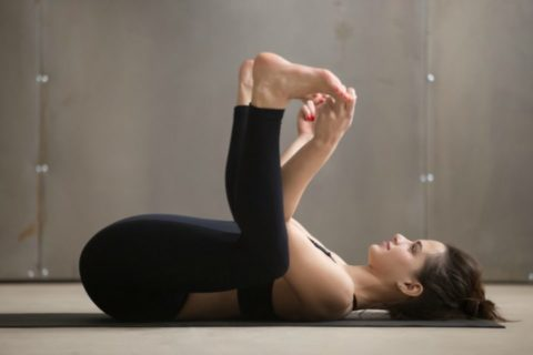 This is an example of the Happy Baby pose - simple yoga exercises for easy yoga in bed.