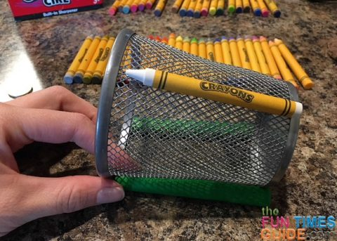 The first crayon glued onto the wire mesh pencil holder.