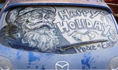 Happy Holidays and Santa Claus drawn in car dust on a dirty windshield.